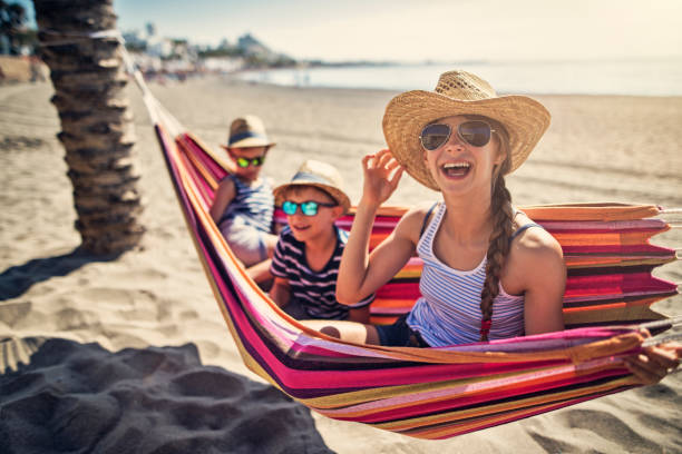 Kids having fun on hammock on beach stock photo