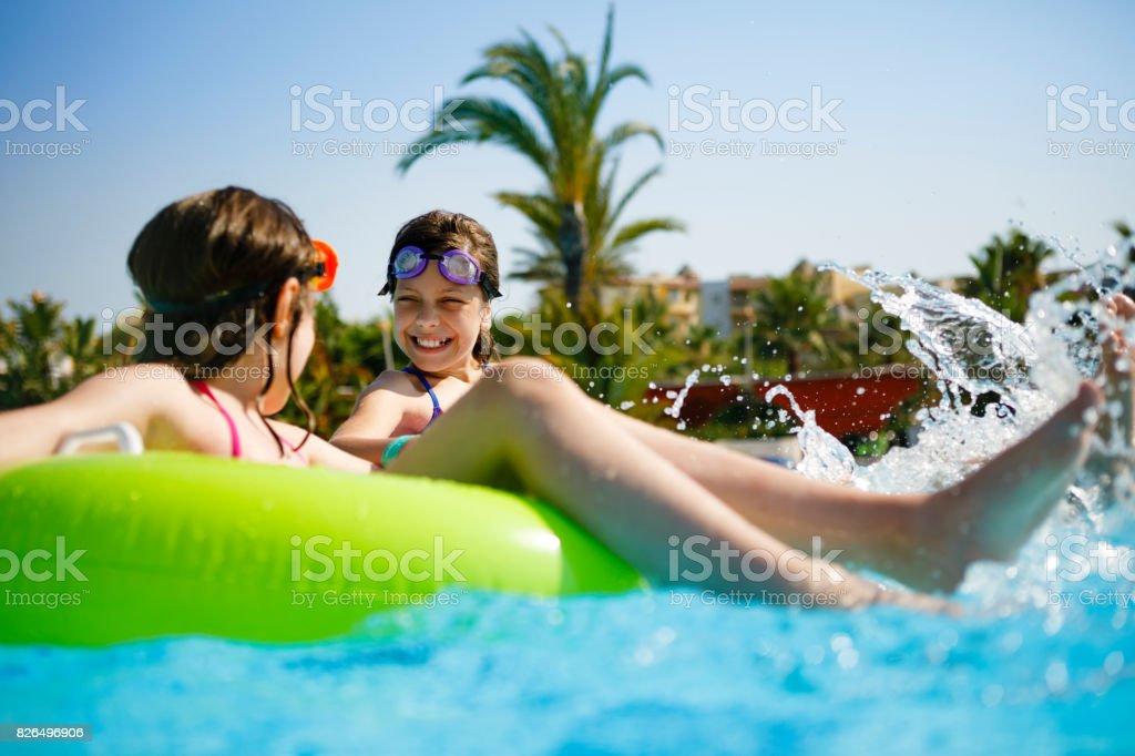 Kids having fun on innertubes in swimming pool stock photo
