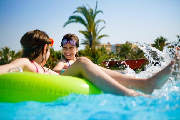 kinder, die spaß am innertubes im schwimmbad - hotels in der türkei stock-fotos und bilder