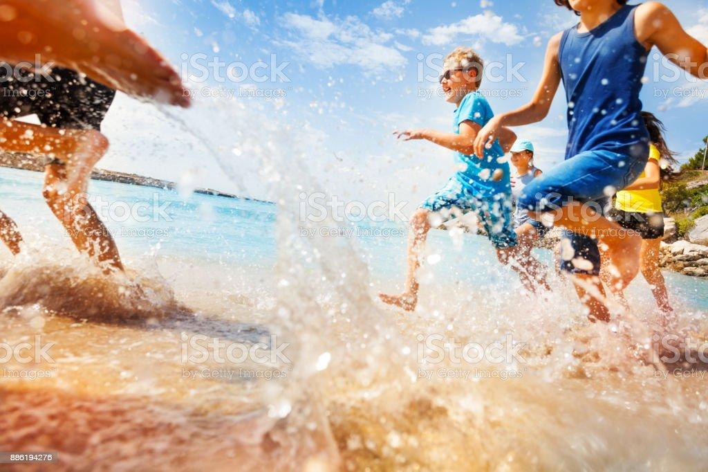 Kids having fun run make splashes in shallow water - foto stock
