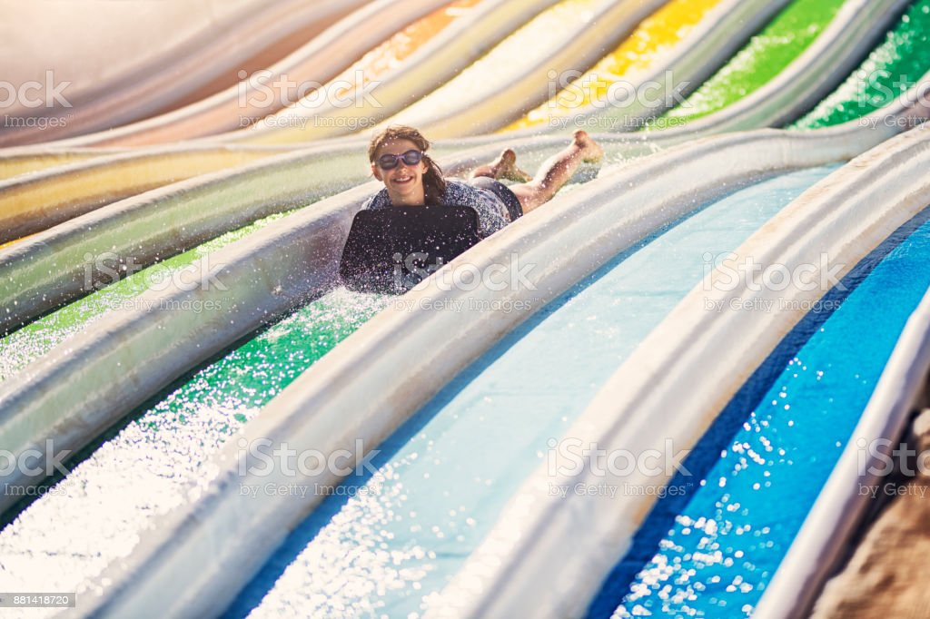 Kids having fun sliding in a waterpark stock photo