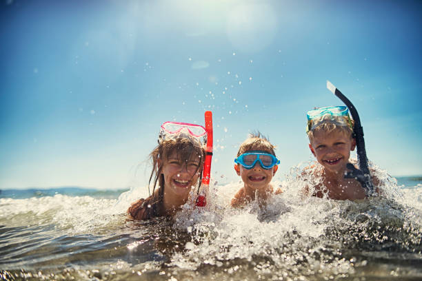 kids having fun snorkeling in beautiful sea - underwater diving stock photos and pictures