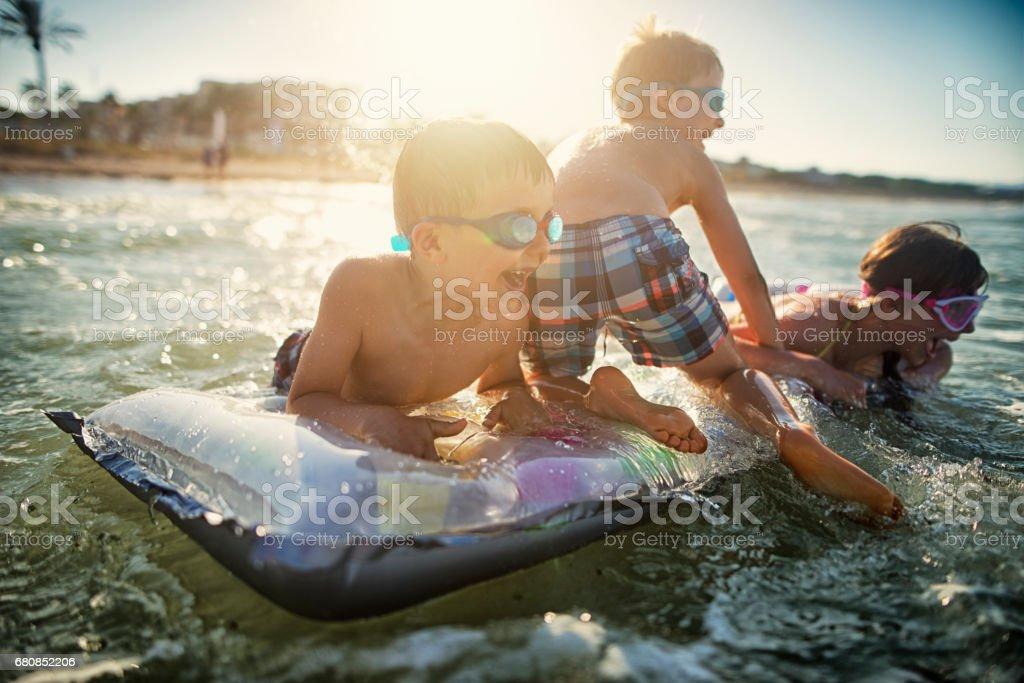 Kids having fun splashing in sea waves on air bed stock photo