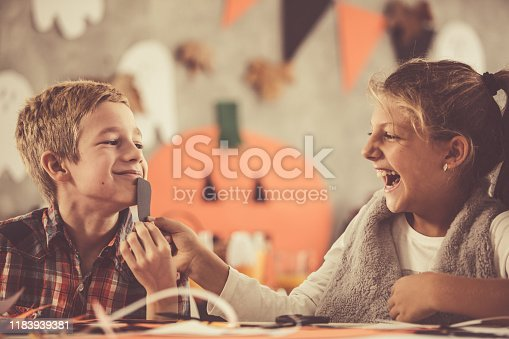 Shot of cheerful boy and girl sitting at the table, having fun and laughing while making beards and mustaches for a Halloween themed party together.