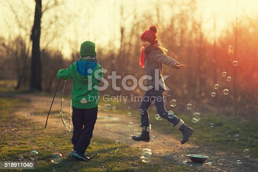 618034312 istock photo Kids having fun with bubbles on early spring 518911040