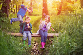 Little boys aged 5 and theirs elder sister aged 9 are playing on the small bridge in the forest. They are enjoying beautiful nature and the sunset, laughing and blowing bubbles,