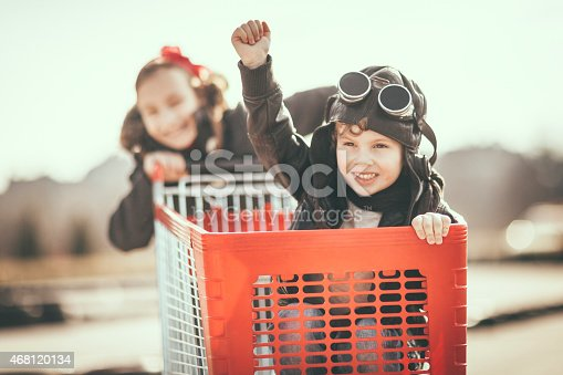 Sister driving her little brother in a shopping cart. Cute little boy is wearing a helmet and protective glasses. Happy siblings are having fun and have large smiles on their faces. Image taken on a kart circuit outdoors. Toned image.