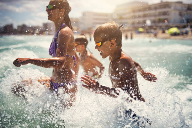 Kids having super fun running in the sea waves stock photo