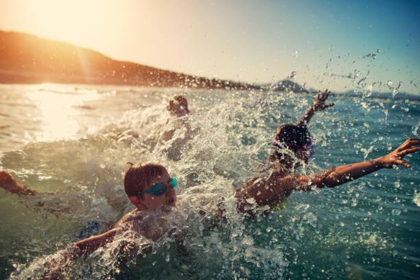 kids having super fun splashing and jumping in the sea waves - nuoto mare foto e immagini stock
