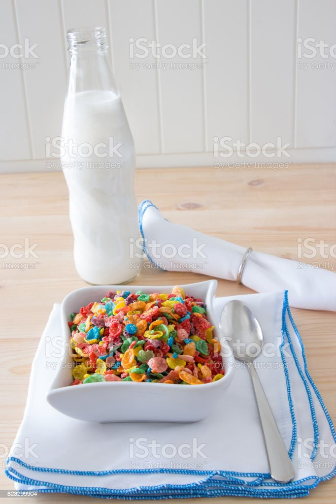 Kids healthy quick breakfast. Colorful rice cereal and bottle milk for kids on wooden background. Copy space stock photo