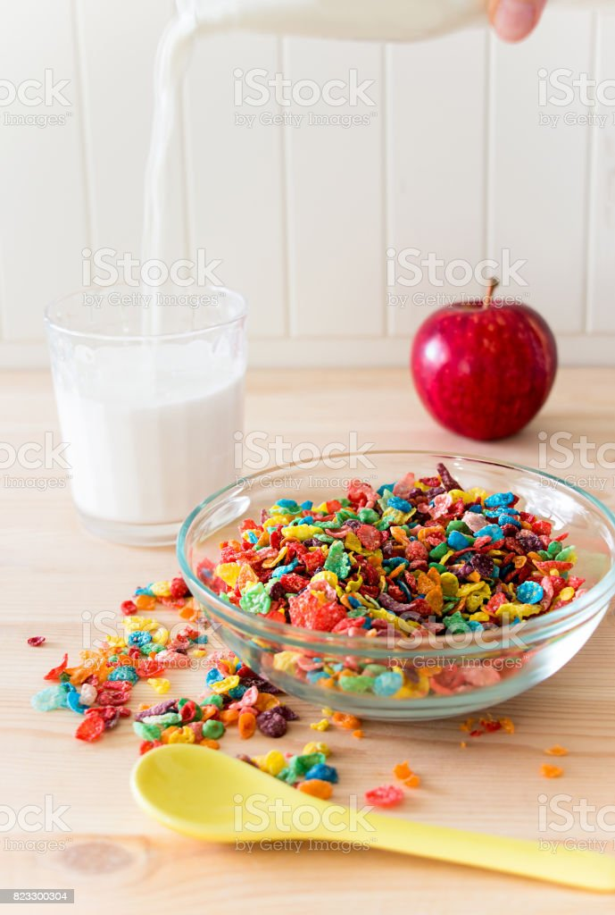 Kids healthy quick breakfast. Colorful rice cereal, flowing milk, apple on wooden background. Copy space stock photo