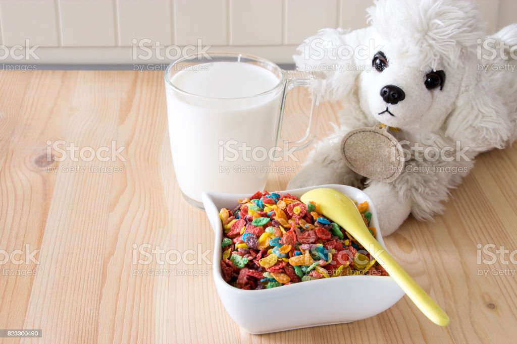 Kids healthy quick breakfast. Colorful rice cereal, milk and dog toy on wooden background. Copy space stock photo