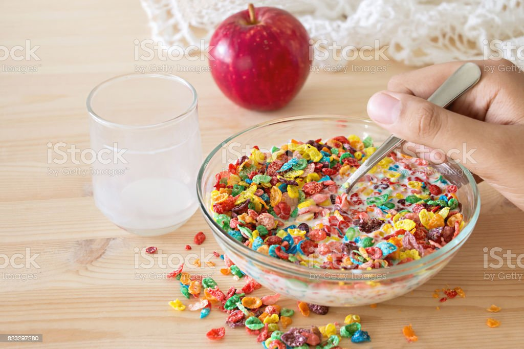 Kids healthy quick breakfast. Colorful rice cereal with milk and apple for kids on wooden background. Copy space stock photo
