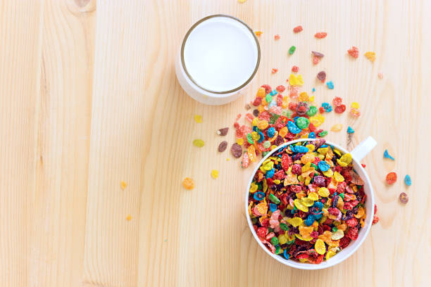 Kids healthy quick breakfast. Colorful rice cereal with milk on wooden background. Copy space stock photo