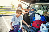 Kids helping to pack the family car for road trip. \nSunny summer day in Italy.\nNikon D850
