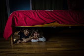Two kids (brother and sister) are hiding under the bed with fear while the brother mute his sister with his hand