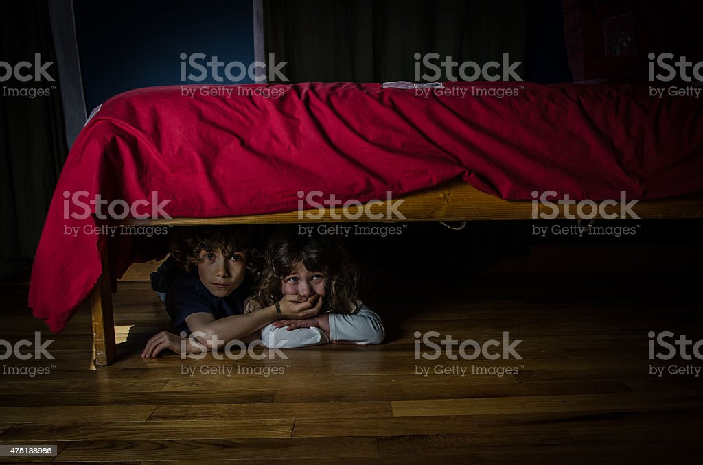 Kids hidden under the bed with fear and crying stock photo
