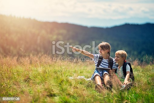 istock Kids hikers checking map on tablet in the grassy meadow 658999106