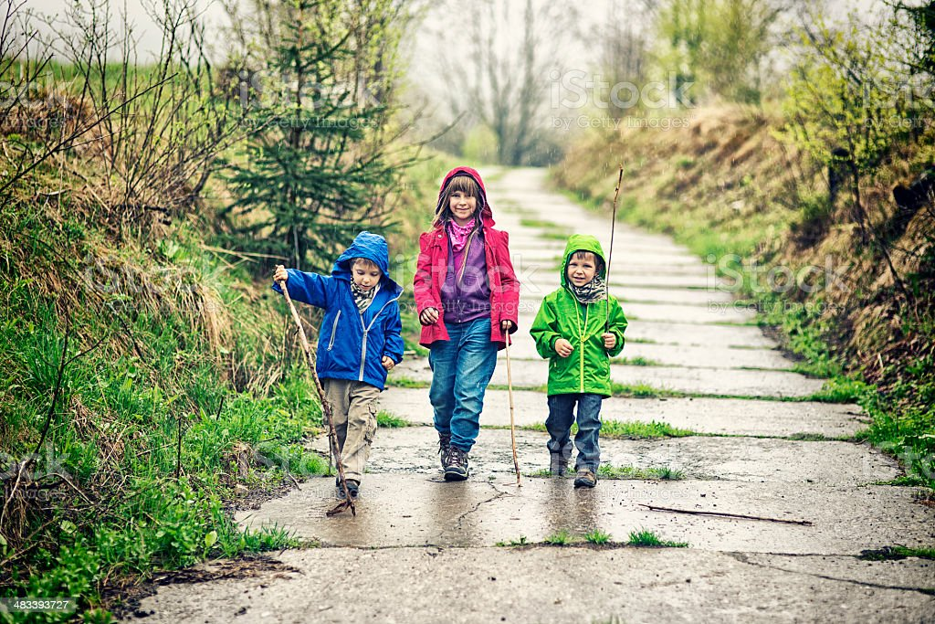 Kids hiking in rain stock photo