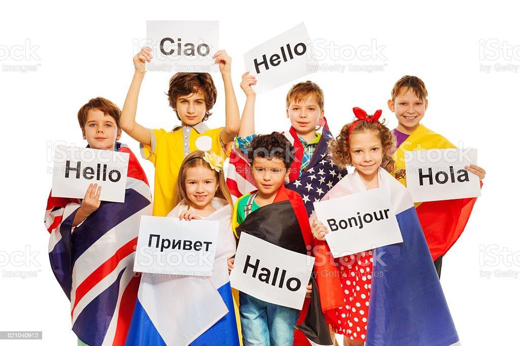Bambini con saluto le indicazioni nelle lingue diverse - foto stock
