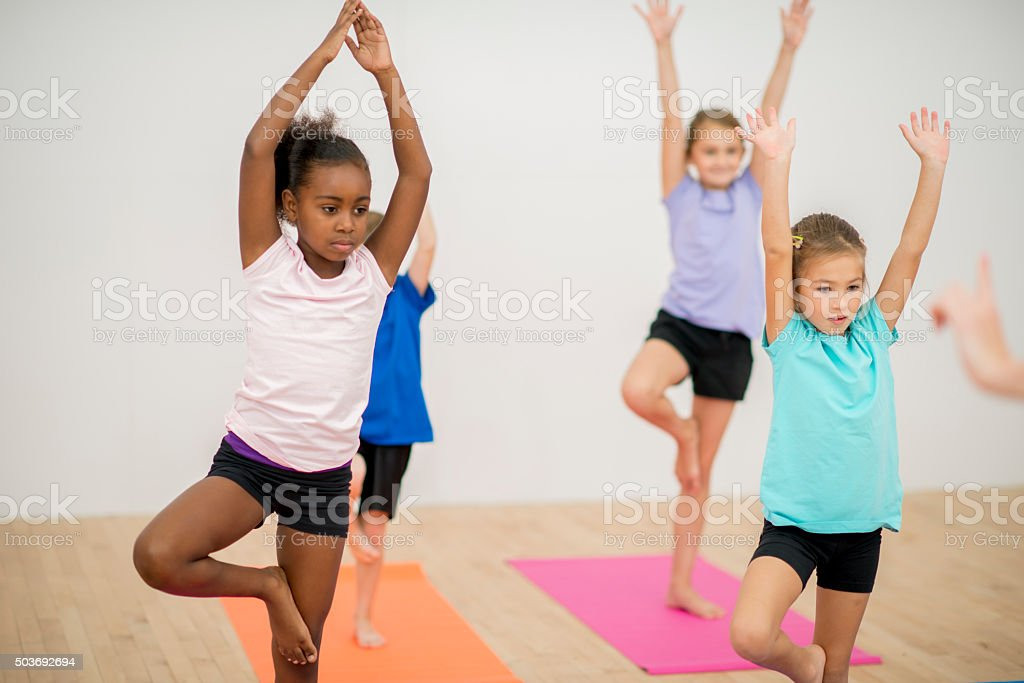 Kids Holding Tree Post in Yoga Class stock photo