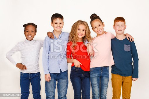 1003539592istockphoto Kids hugging and looking at camera against white background 1092670736