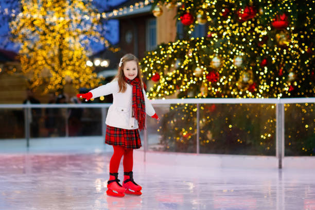 Kids ice skating in winter. Ice skates for child. Kids ice skating in winter park rink. Children ice skate on Christmas fair. Little girl with skates on cold day. Snow outdoor fun for child. Winter sports. Xmas family vacation with kid. ice rink stock pictures, royalty-free photos & images