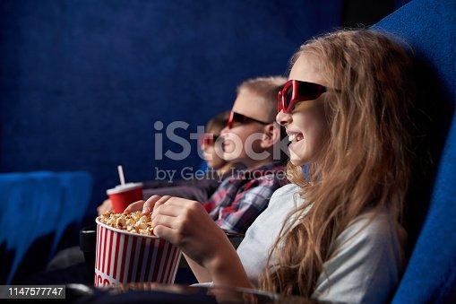 istock Kids in 3d glasses smiling, watching movie in cinema. 1147577747