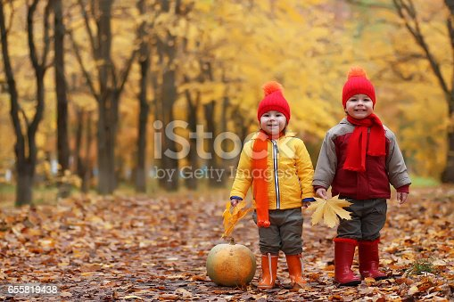 istock kids in autumn park with pumpkin 655819438