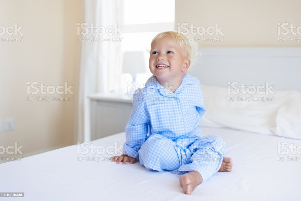 Kids playing in parents bed. Children wake up in sunny white bedroom....