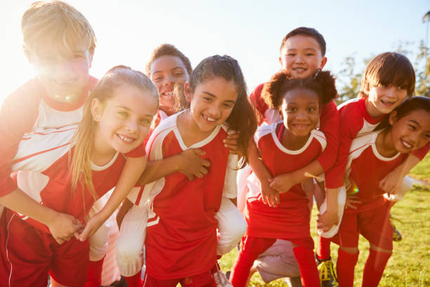Kids in elementary school sports team piggybacking outdoors Kids in elementary school sports team piggybacking outdoors sport stock pictures, royalty-free photos & images
