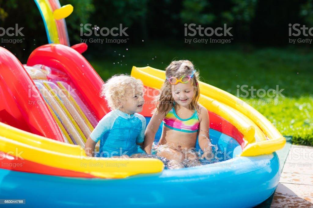 Kids in garden swimming pool with slide foto de stock royalty-free