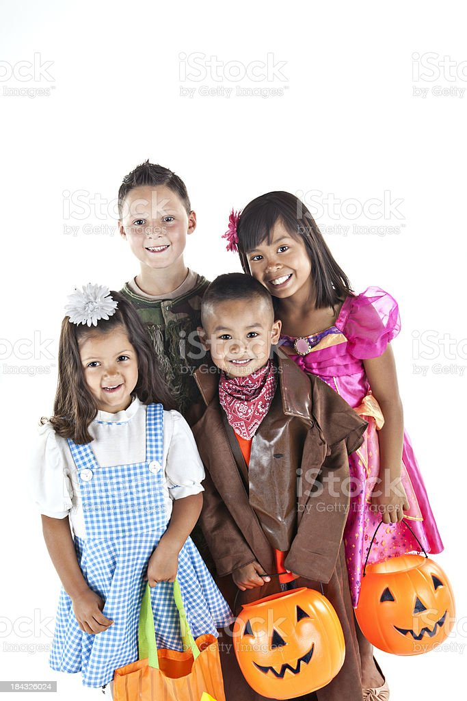 Kids in halloween costumes standing together and smiling royalty-free stock photo