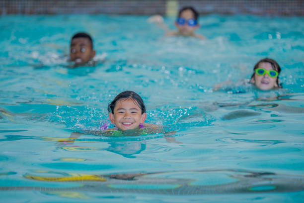 Kids in indoor pool Four kids are swimming in an indoor pool. They are paddling towards the camera. The girl in the front is smiling at the camera. Two of the kids are wearing goggles. community center stock pictures, royalty-free photos & images
