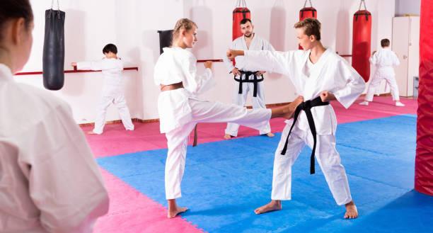 enfants en kimono exercer des techniques en paire pendant la classe de taekwondo au gymnase - arts martiaux photos et images de collection