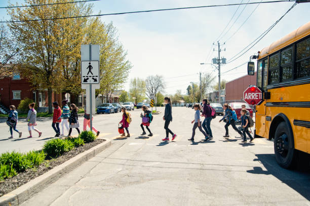 Kids in line crossing street getting out of school bus. stock photo