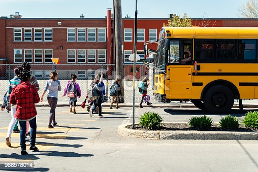 Large group of multi-ethnic elementary age school kids crossing the street in line to get on the school bus. School in the background. Most of them are carrying backpack and lunch box. Horizontal full length outdoors shot on a bright sunny day with copy space.