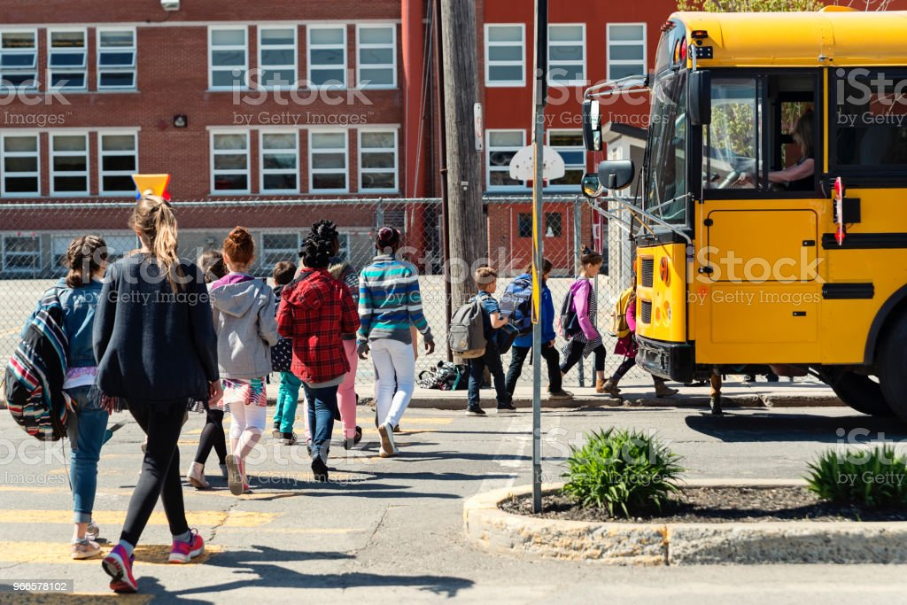 Kids in line crossing street to get on school bus. stock photo