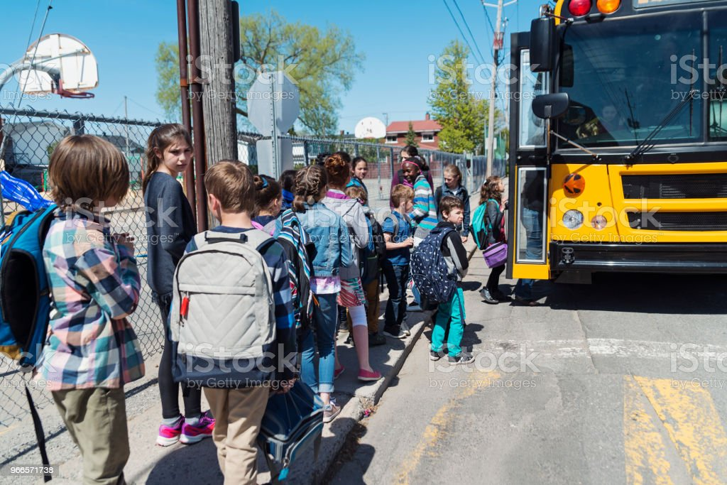 Kids in line waiting to get on school bus. stock photo