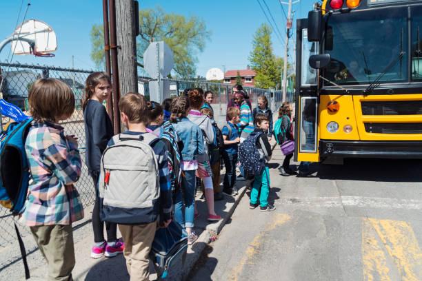Kinder in der Schlange, auf Schulbus zu erhalten. – Foto