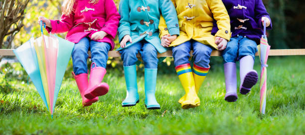 Kids in rain boots. Foot wear for children. Group of kids in rain boots. Colorful footwear for children. Boys and girl in rainbow wellies and duffle coat. Rainbow foot wear and clothing for autumn or winter. Rainy weather outerwear and fashion. coat garment stock pictures, royalty-free photos & images