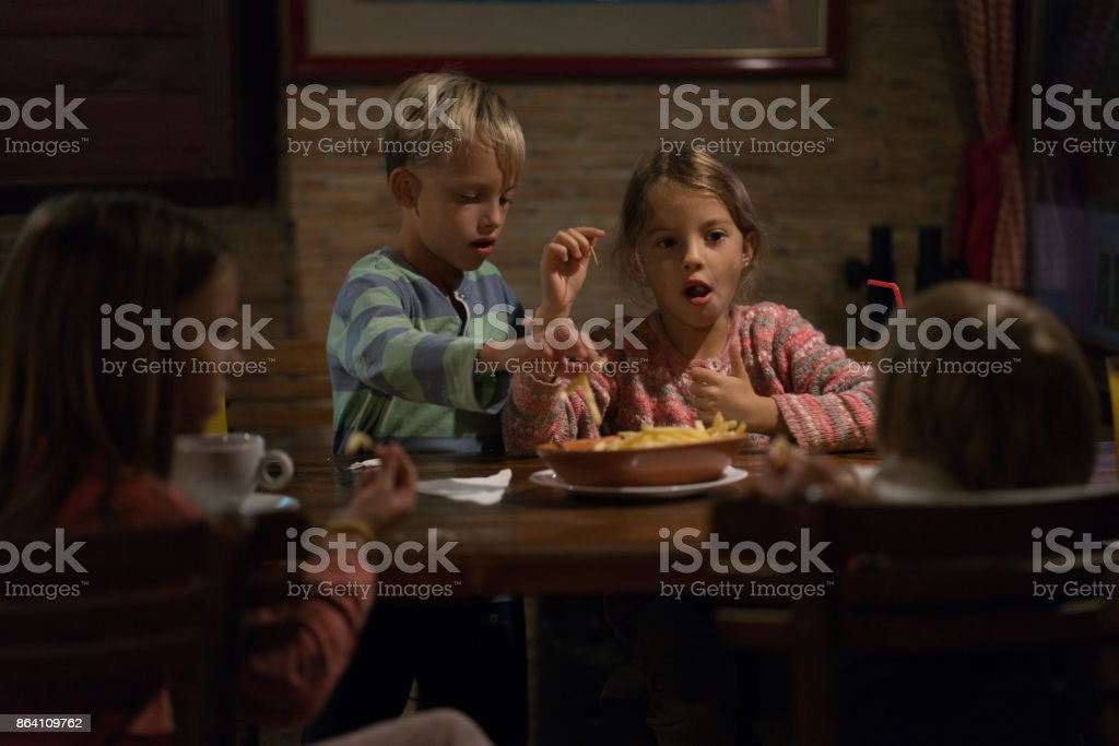 Kids in restaurant eating french fries royalty-free stock photo