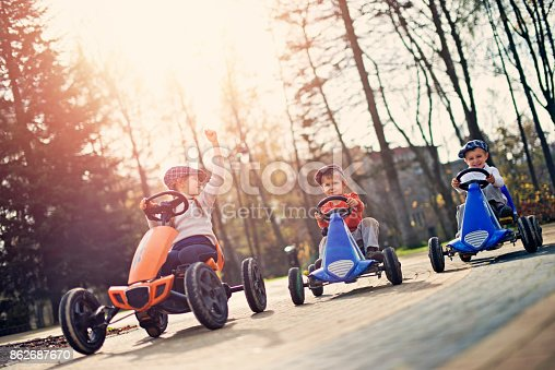 Kids racing in small cars in the park. Little girl is winning. Sunny autumn day.