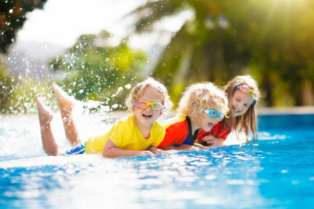 Kids in swimming pool. Children swim. Family fun. Kids play in swimming pool. Children learn to swim in outdoor pool of tropical resort during family summer vacation. Water and splash fun for young kid on holiday. Sun protection for child and baby. swimming goggles stock pictures, royalty-free photos & images