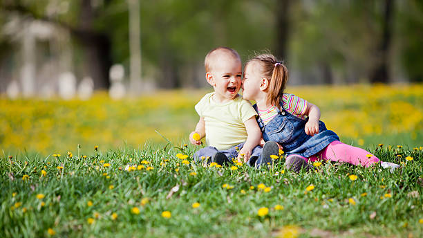 kids in the field - little girls little boys kissing love stock photos and pictures