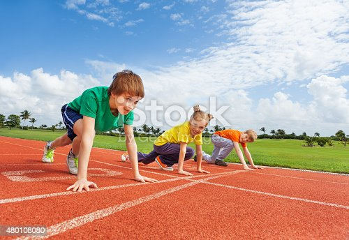 istock Kids in uniforms on bended knee ready to run 480108080