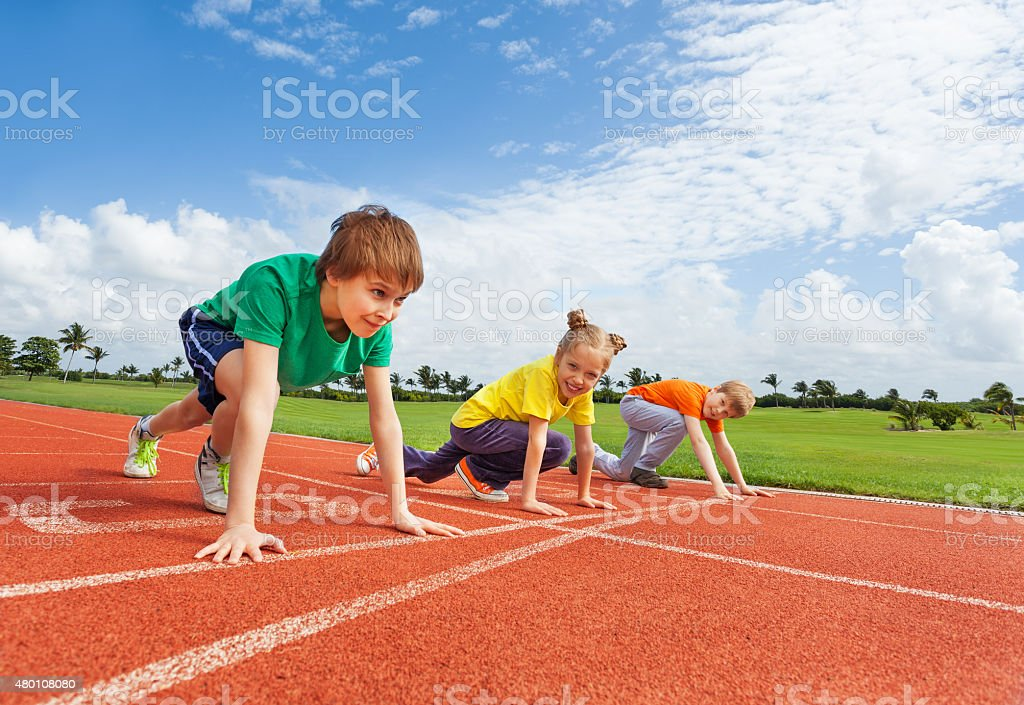 Kids in uniforms on bended knee ready to run stock photo