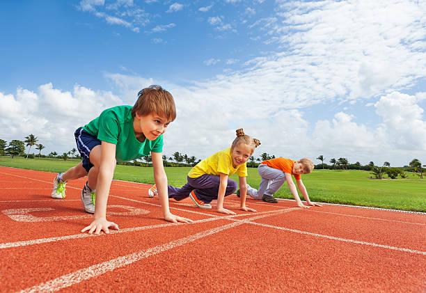 crianças em uniformes em bended joelho pronto para correr - atletismo - fotografias e filmes do acervo