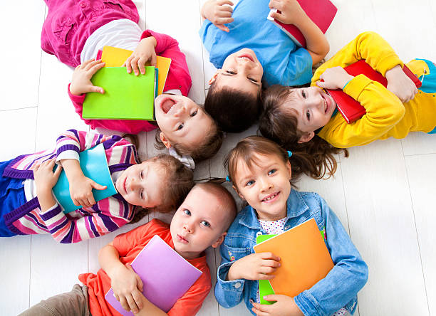 Kids in vibrant colored clothes laying with heads together Six  kids with books lying  on the floor together. Top view preschool student stock pictures, royalty-free photos & images