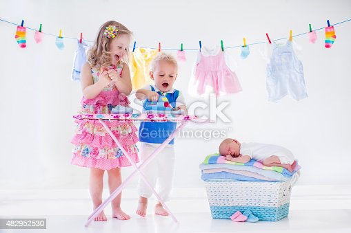 954356678istockphoto Kids ironing clothes for baby brother 482952530